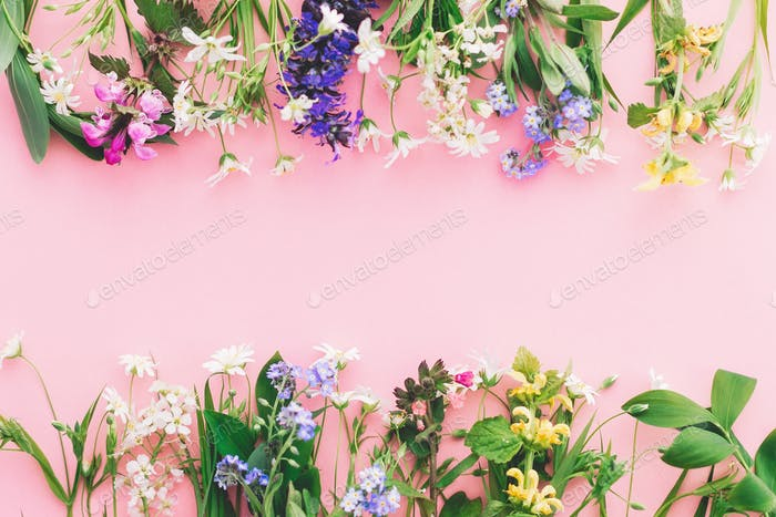 Wildflowers colorful frame on pink paper background, flat lay with space for text