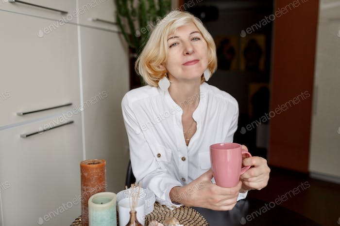 50-year-old  blonde woman holding cup of tea and sitting at modern kitchen.