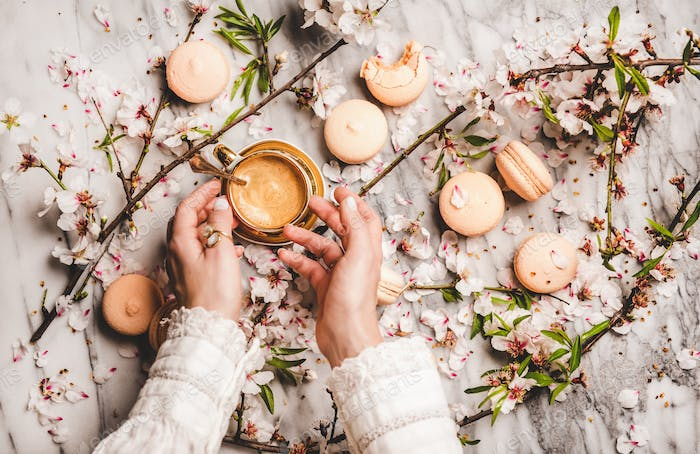 Womans hands over espresso coffee, macaron cookies and flowers