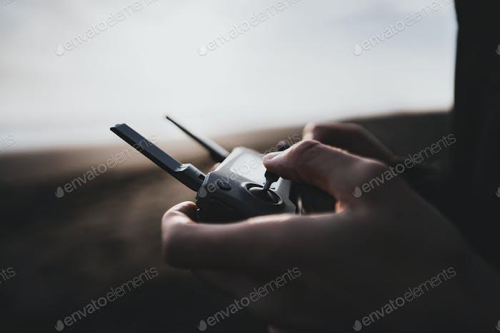 Hombre controlando un Zumbido tripulado por un mando a distancia