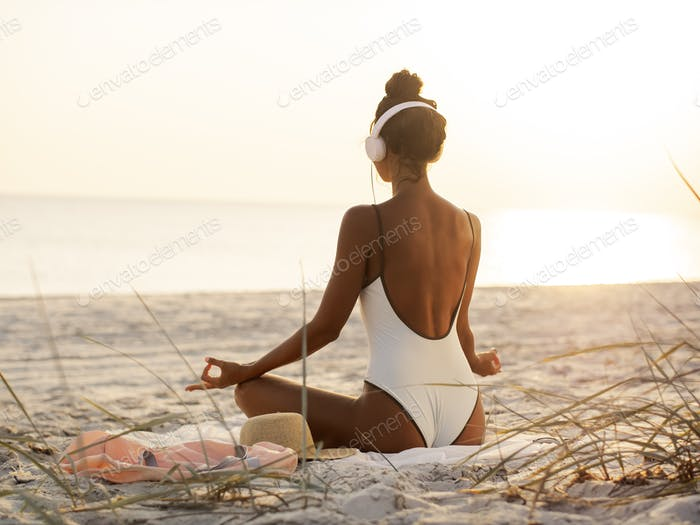 Woman in Yoga Meditation Pose with Headphones on the Beach