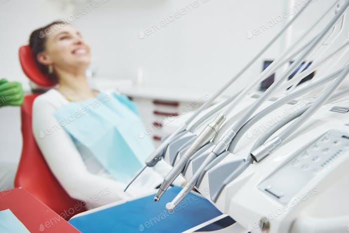 Junge Patientin sitzt auf einem Stuhl in der Zahnarztpraxis. Vorbereitung auf die zahnärztliche Untersuchung