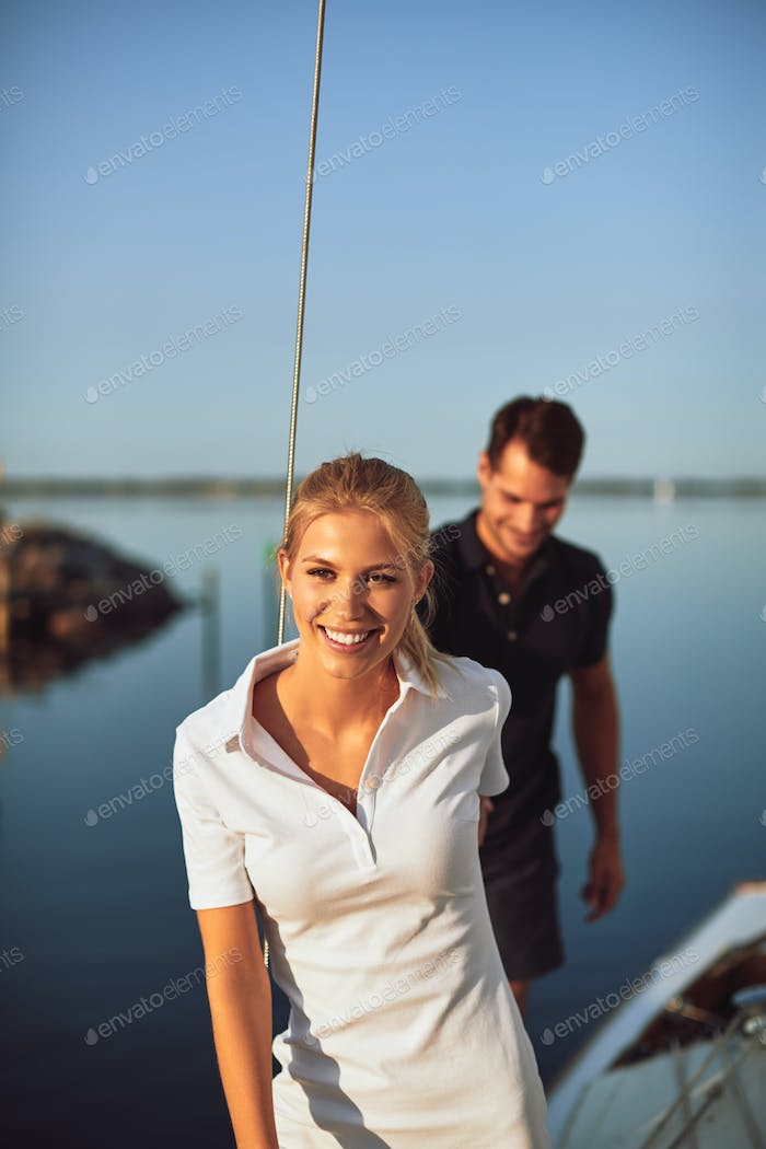 Smiling woman and her husband walking together on their yacht