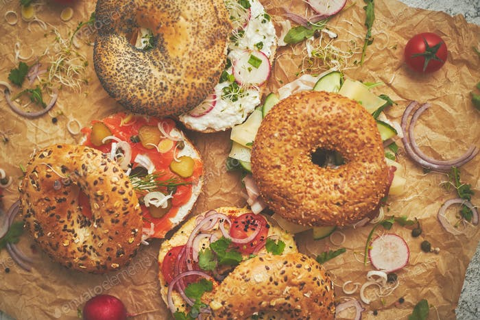 Tasty colorful various bagels with healthy ingredients served on brown baking paper
