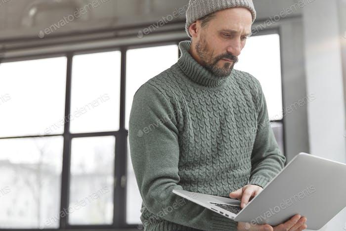 Periodista masculino experimentado de mediana edad concentrada lee las últimas noticias en páginas web, búsquedas informan