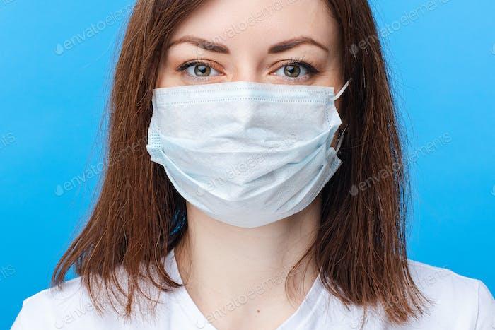 Mujer contra el virus corona en máscara. fondo azul claro