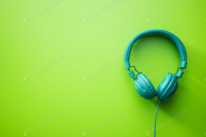 Auriculares estéreo con cable verde sobre fondo verde.