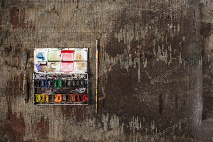 Pinsel und Röhren von Ölfarben auf Holzhintergrund
