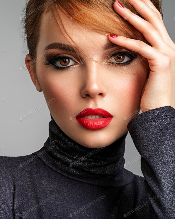 Beautiful brunette girl with red lips and short, slick hair.