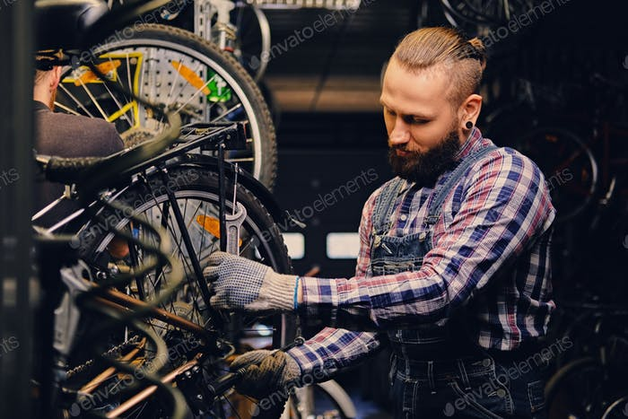 Mechaniker tun Fahrrad Rad Service Handbuch in einer Werkstatt.