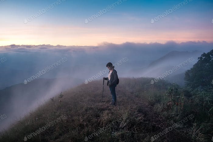 Girl standing on top of the mountain surrounded by fog