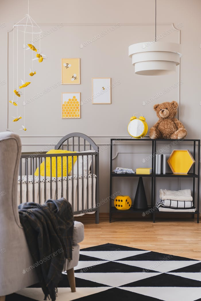 Vertical view of stylish grey and yellow baby bedroom with crib