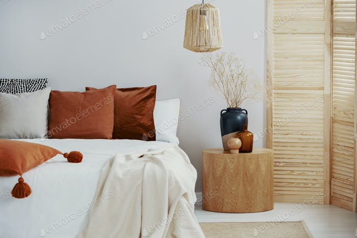 Dark orange and grey pillow on king size bed, copy space on empt