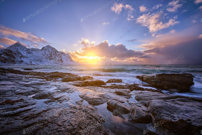 Coast of Norwegian sea on rocky coast in fjord on sunset