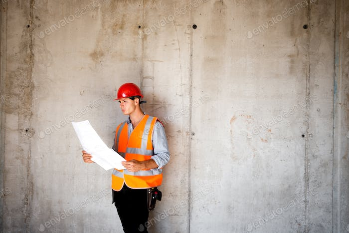 Man dressed in orange work vest and helmet explores construction documentation on a concrete wall