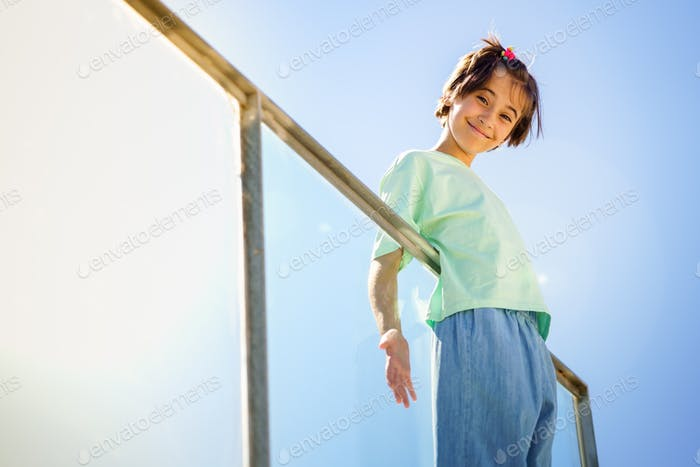 9-year-old girl posing happily on a staircase