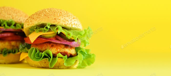 Fast food banner. Juicy meat burgers with cheese, lettuce on yellow background. Take away meal