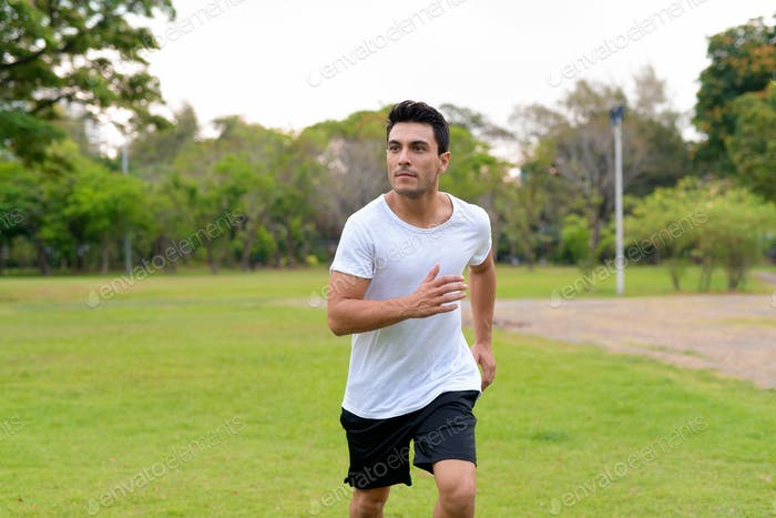 Young handsome Hispanic man jogging in the park outdoors