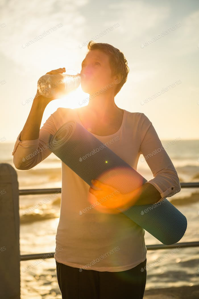 Sporty woman with exercise mat drinking water at promenade