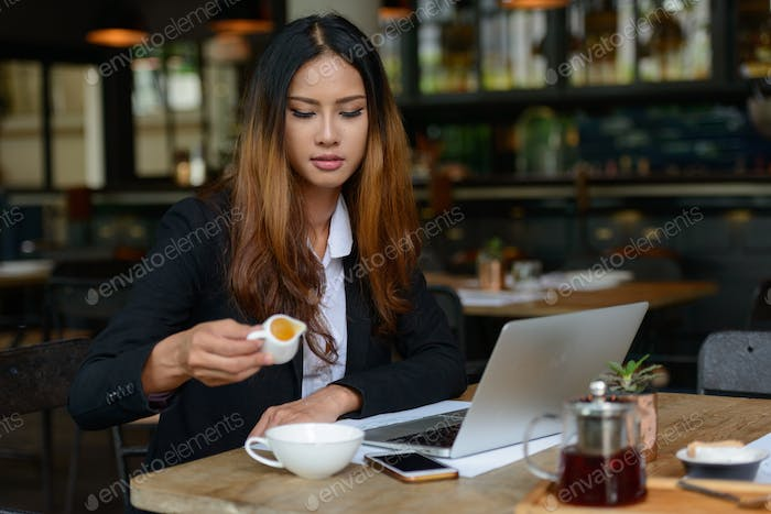Young beautiful Asian businesswoman drinking coffee at the coffee shop