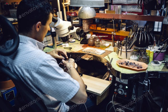 Jeweler working with optical device
