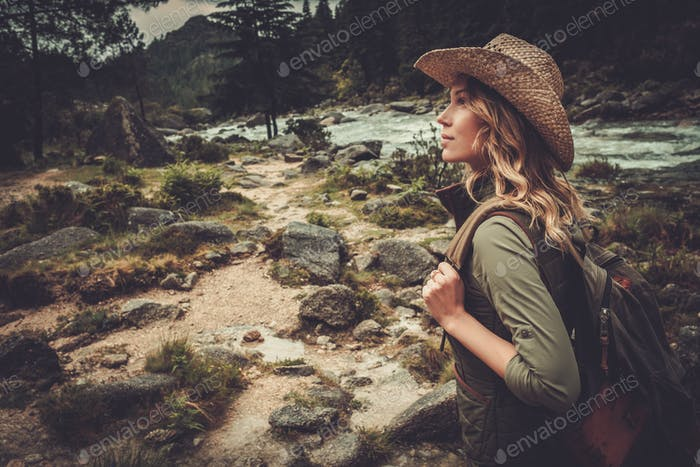 Beautiful woman hiker walking near wild mountain river.