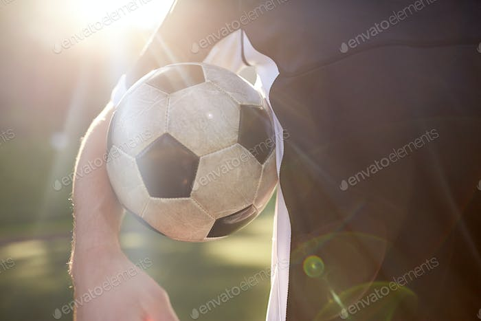 close up of soccer player with ball on field