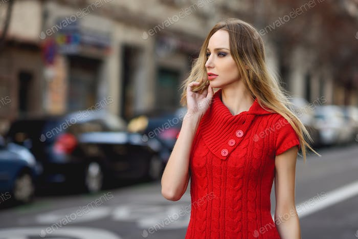 Young blonde woman looking at something in the street