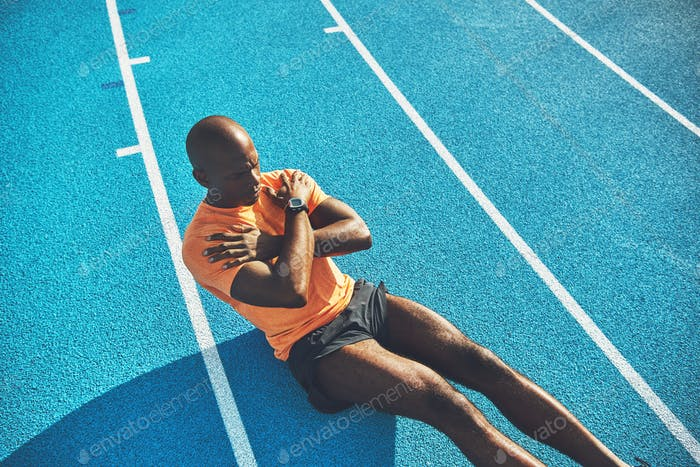 Young African athlete doing crunches on a running track