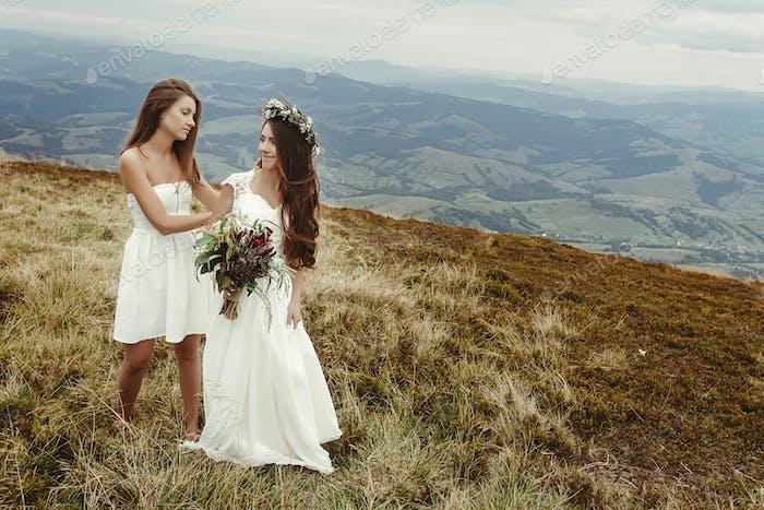 стильная невесты, помогающая великолепной невесте подготовка