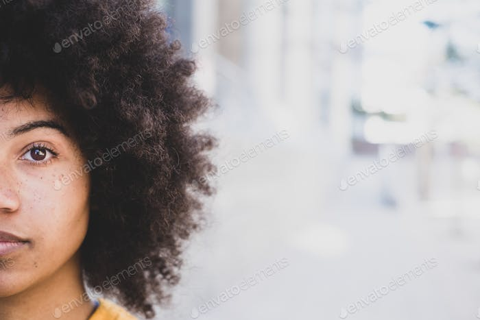 portrait of half a face of one young beautiful African or American woman looking at the camera.