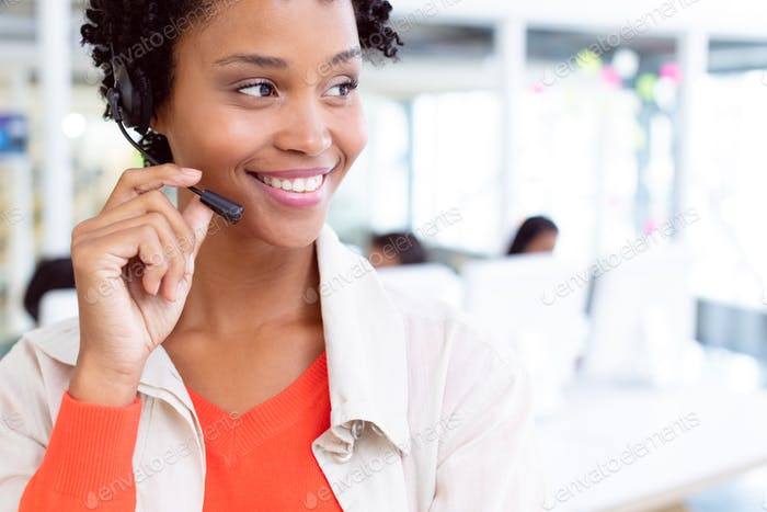 Happy African-american female customer service executive standing with headset