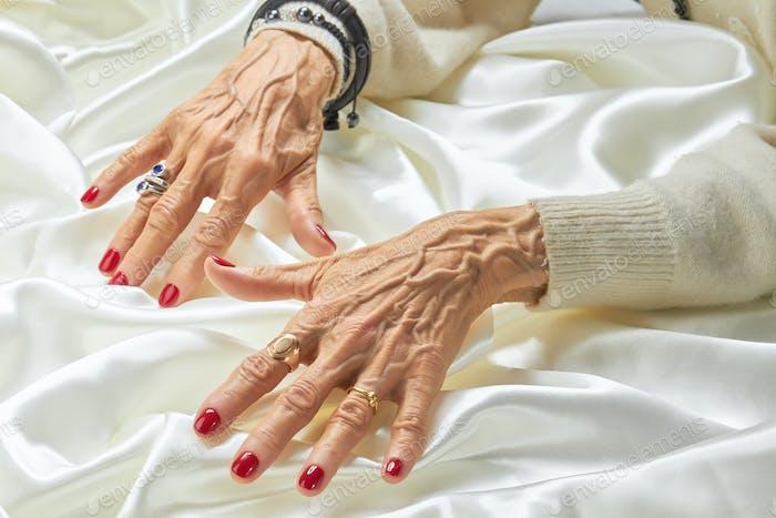 Senior gepflegte Hände mit Schmuck auf Seide