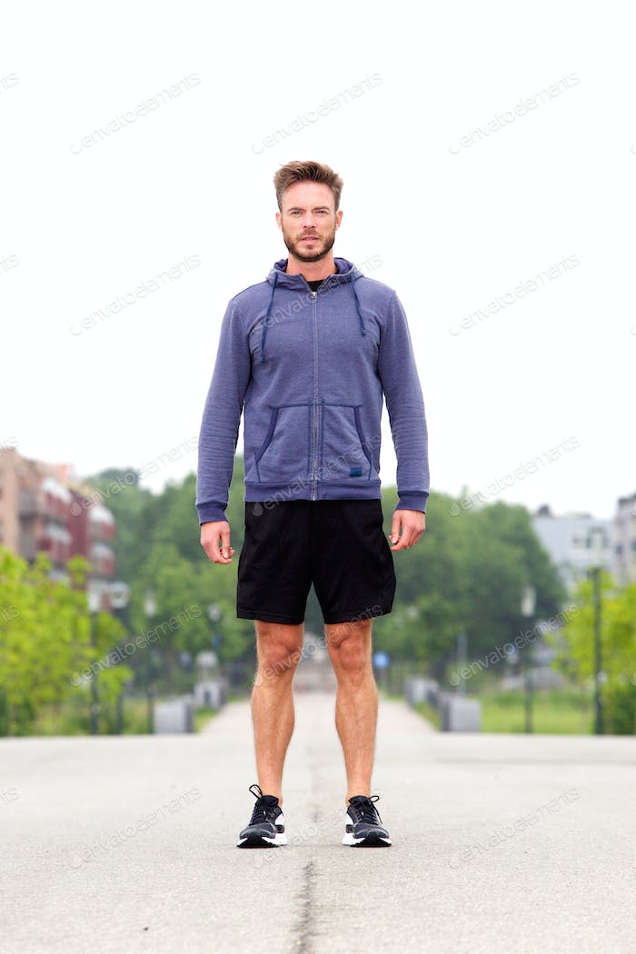 Attractive male athlete standing in middle of street