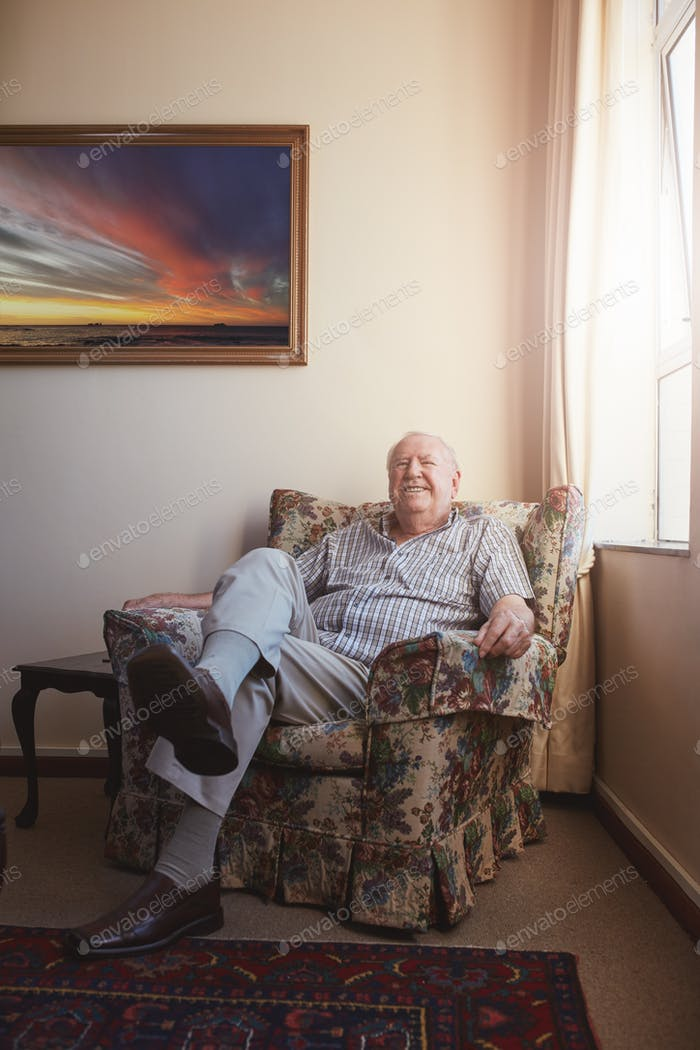 Old man relaxing on an arm chair at home