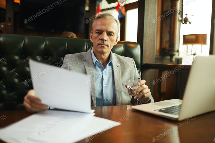 Man with documents in cafe