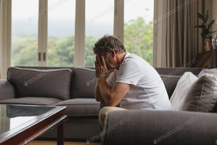Trauriger aktiver älterer kaukasischer Mann, der sein Gesicht mit den Händen bedeckt, während er auf dem Sofa sitzt