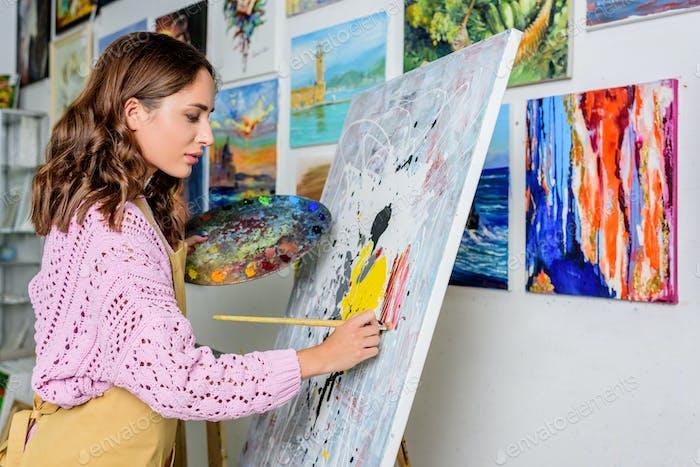 side view of beautiful female artist painting in workshop
