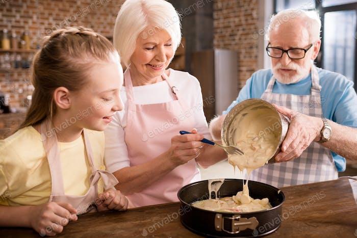glückliche Großeltern und Mädchen kochen zusammen zu Hause