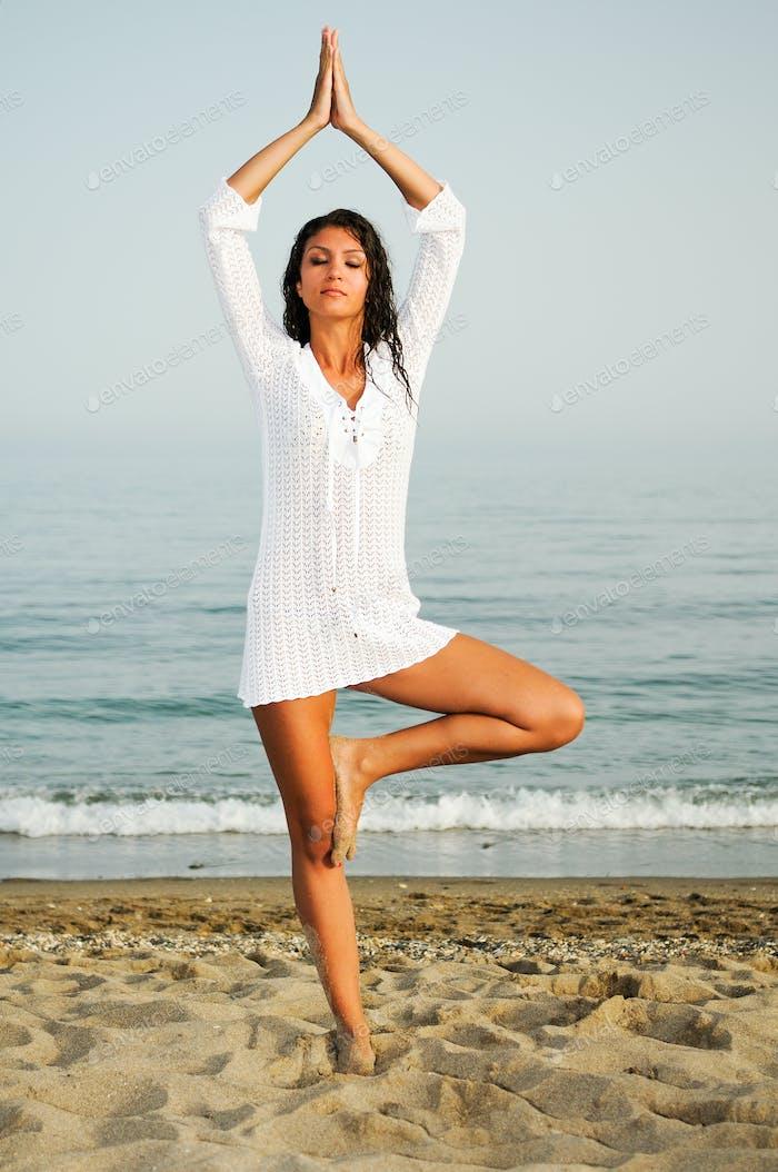Pretty woman doing yoga on the beach