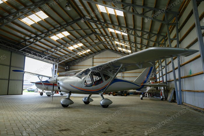 outdoor shot of small plane standing in shed