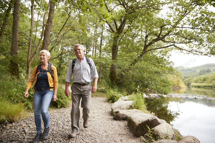Senior Couple Hiking Along Path By River In UK Lake District