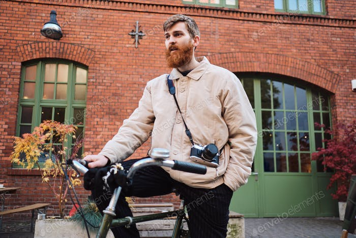 Young attractive bearded man standing with old classic bicycle on street
