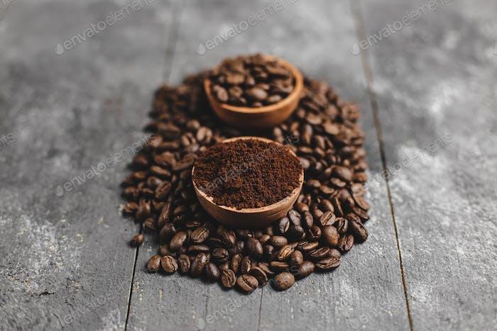 gemahlener Kaffee in Holz Untertasse mit grunge schwarzem Hintergrund