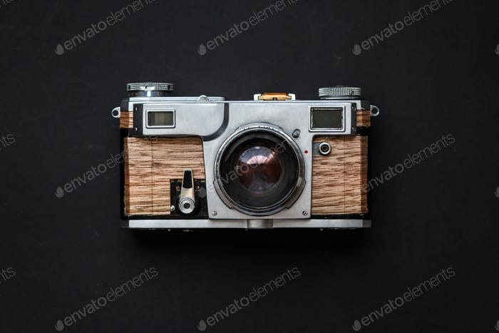 Old analog photo camera with wooden body on black background