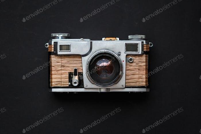 Alte analoge Fotokamera mit Holzkörper auf schwarzem Hintergrund