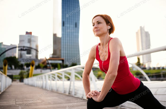Young woman runner with earphones in city, stretching