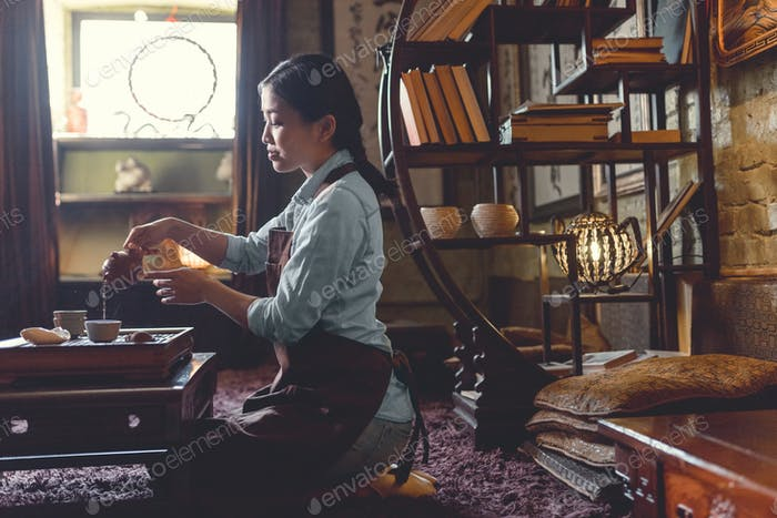 Young woman pouring tea in room