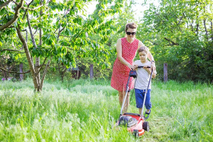 Mutter und Sohn mähen Gras mit Rasenmäher