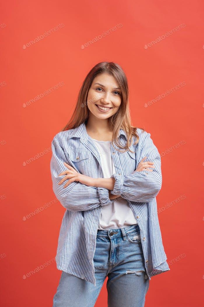 Süße langhaarige weibliche posiert mit gekreuzten Armen, lächelnd Gesichtsausdruck auf rotem Hintergrund.